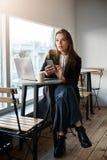 Можете вы принести получение пожалуйста Крытая съемка стильной симпатичной современной женщины в местном кафе сидя около окна Стоковые Изображения RF