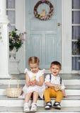 Мои сестра и младший брат сидя на лестницах дома и стоковая фотография
