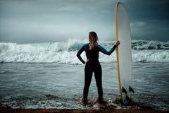 Мокрая одежда женщины серфера нося стоя на пляже с surfboard Стоковое Фото