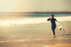 мокрая одежда молодой девушки серфера нося идя в океан Стоковое фото RF