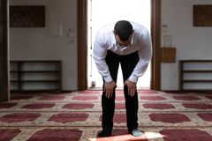 Молитва скромного бизнесмена мусульманская в мечети стоковые изображения