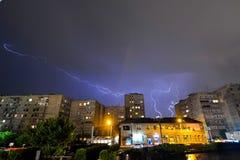 Молния в ночном небе над домами стоковое фото