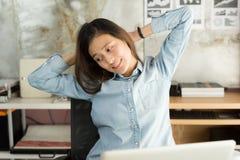 Молодая азиатская бизнес-леди сидя на простирании стула oneself стоковое фото