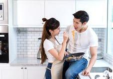 Молодая азиатская девушка держа лоток с спагетти черпает фидер ложкой к парам молодого человека стоковая фотография rf