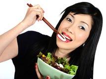 Молодая азиатская девушка есть салат Стоковые Изображения RF