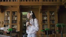 Молодая азиатская женщина в белых рубашке и стеклах слушая к музыке акции видеоматериалы