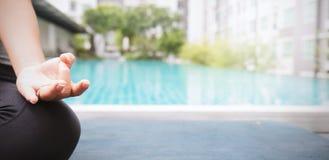 Молодая азиатская женщина делая движения йоги или размышляя бассейном, стоковая фотография