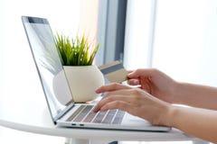 Молодая азиатская женщина держа кредитную карточку и используя портативный компьютер Стоковое Изображение RF