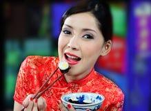 Молодая азиатская женщина есть суши Стоковая Фотография RF