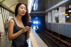 Молодая азиатская женщина используя мобильный телефон на вокзале стоковое фото