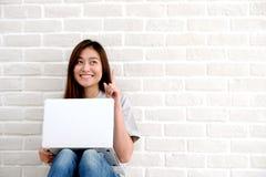Молодая азиатская женщина используя портативный компьютер сидя перед whit стоковые фотографии rf
