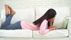 Молодая азиатская женщина используя прибор компьтер-книжки с зеленым экраном сток-видео