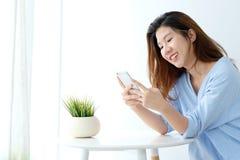 Молодая азиатская женщина используя умный телефон с ослабляет эмоцию на белизне Стоковые Фото