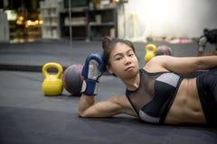 Молодая азиатская женщина кладя на пол в спортзале фитнеса стоковое фото