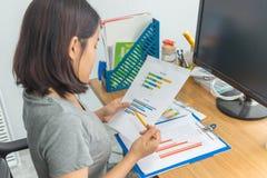 Молодая азиатская женщина офиса в случайной носке анализируя финансовые данные по диаграммы стоковые фотографии rf