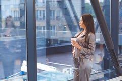 Молодая азиатская женщина при чашка стоя против окна Стоковые Фотографии RF