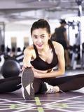 Молодая азиатская женщина протягивая ноги в спортзале Стоковое Фото