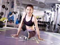 Молодая азиатская женщина протягивая ноги в спортзале Стоковая Фотография