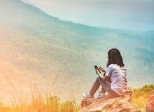 Молодая азиатская женщина сидит на утесе на скале и использовании умного телефонного сообщения к ее друзьям пока на каникулах на  стоковое изображение rf