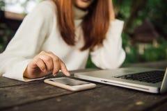 Молодая азиатская женщина сидя в кофейне на деревянном столе, азиатская женщина используя smartphone На таблице компьтер-книжка Стоковые Фотографии RF