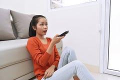 Молодая азиатская женщина смотря телевидение пока сидящ Стоковые Изображения