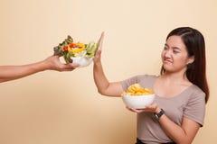 Молодая азиатская женщина с картофельными стружками говорит нет к салату Стоковое Фото