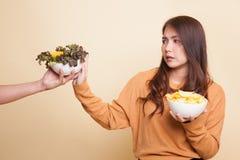 Молодая азиатская женщина с картофельными стружками говорит нет к салату Стоковое Изображение RF