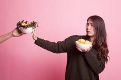 Молодая азиатская женщина с картофельными стружками говорит нет к салату Стоковое фото RF