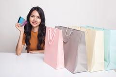 Молодая азиатская женщина с хозяйственной сумкой и пустой карточкой Стоковая Фотография RF
