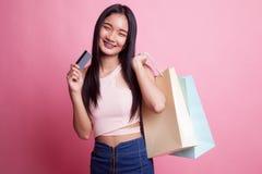 Молодая азиатская женщина с хозяйственной сумкой и пустой карточкой Стоковое фото RF