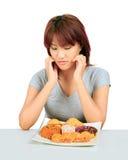 Молодая азиатская женщина с donuts на таблице Стоковое Изображение