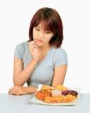 Молодая азиатская женщина с donuts на таблице Стоковое Фото