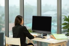 Молодая азиатская коммерсантка в костюме сидя перед компьютером b стоковая фотография rf