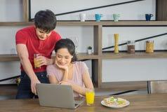 Молодая азиатская пара, в случайном платье, и смотреть к ноутбук компьютера совместно стоковое фото