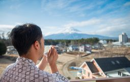 Молодая азиатская стойка человека смотря Mount Fuji стоковые фото