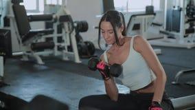 Молодая активная девушка поднимает гантель для сидя бицепса видеоматериал