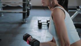 Молодая активная девушка поднимает гантель для сидя бицепса сток-видео