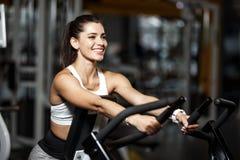 Молодая атлетическая девушка одетая в sportswear делая тренировки с особенным оборудованием спорта в современном спортзале стоковая фотография