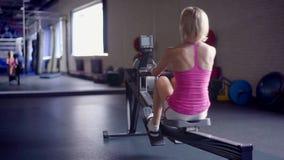 Молодая атлетическая женщина делая разминку машины rowing на спортзале акции видеоматериалы