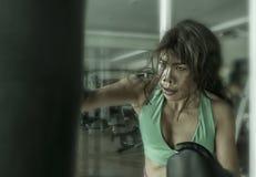 Молодая атлетическая и подходящая привлекательная азиатская женщина бойца пробивая тяжелую сумку с перчатками бокса на спортзале  стоковое изображение rf