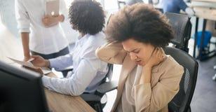 Молодая африканская бизнес-леди имея стресс и головную боль в офисе стоковое изображение