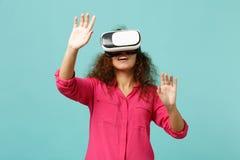 Молодая африканская девушка смотря в шлемофоне, касании что-то как нажим нажимает на кнопке, указывая на плавая виртуальный экран стоковое фото rf