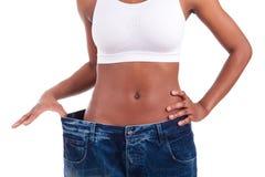 Молодая африканская женщина в старых джинсыах задыхается после проигрышного веса стоковые изображения