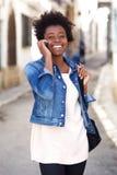 Молодая африканская женщина идя и говоря на мобильном телефоне Стоковые Изображения