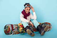 Молодая африканская женщина изолированная на голубой концепции сноубординга спорта зимы студии стены сидя с доской стоковая фотография rf
