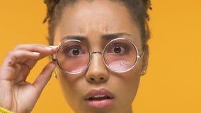 Молодая африканская женщина принимая eyeglasses смотря сотрясенный на камере, дерматологии акции видеоматериалы