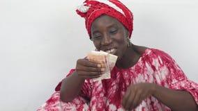 Молодая африканская женщина сидя и подсчитывая ее деньги акции видеоматериалы