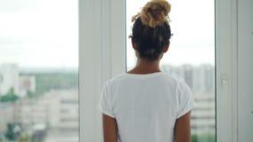 Молодая Афро-американская девушка идет к окну дома и разделяет занавесы после этого наслаждаясь взглядом от окна видеоматериал
