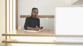 Молодая афро-американская девушка на приеме печатает что-то на мобильном телефоне и после этого пишет вниз крыто сток-видео