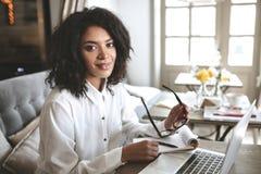 Молодая Афро-американская девушка работая на компьтер-книжке в ресторане Милая дама при темное вьющиеся волосы сидя на кафе с Стоковая Фотография RF
